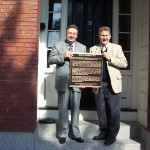 Kim R. Wilson, chairman of the MHSF, and Fred E. Woods, executive director of the MHSF, hold up the plaque in front of the Nathaniel H. Felt home.  Photo courtesy Fred E. Woods