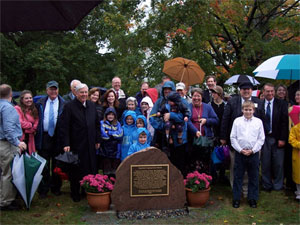 Elder M. Russell Ballard, on left side in dark overcoat, stands with attenders at dedication of plaque marking ancestral homestead in Massachusetts of Prophet Joseph Smith. Courtesy Jonathan Wisco