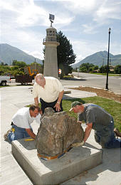 Richard Johnson, left, David Ashby and Clark Taylor place a rock from the Westman Islands in the plaza of the existing Icelandic memorial in Spanish Fork. Photo by Keith Johnson, Deseret Morning News