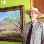 """Las Vegas Old Mormon Fort park ranger Chris Macek stands in front of """"A Gamble in the Desert,"""" by Ken Corbett which MHSF donated.  Photo courtesy Fred E. Woods"""
