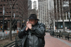 The statue's creator, Dee Jay Bawden, blows a Mormon hymn on the harmonica. Photo by Carl Glassman
